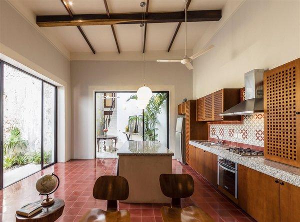 Modern home with kitchen, wood counter, wood cabinet, ceramic tile backsplashe, ceramic tile floor, ceiling lighting, refrigerator, pendant lighting, and drop in sink. Photo  of Casa RC80