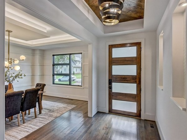 Modern home with hallway and medium hardwood floor. The foyer of the home with wood inlaid tray ceiling and art niches.  Photo 3 of Contemporary Craftsman Home