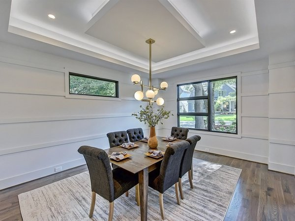 Modern home with dining room, table, chair, recessed lighting, ceiling lighting, medium hardwood floor, and accent lighting. The dining room with modern wainscotting with tray ceiling with LED uplighting Photo 4 of Contemporary Craftsman Home