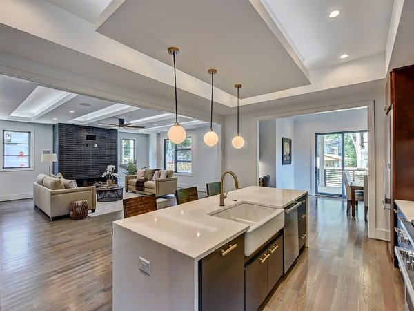 Modern home with kitchen, wood cabinet, light hardwood floor, accent lighting, undermount sink, engineered quartz counter, glass tile backsplashe, and ceiling lighting. Open floorplan Photo 7 of Contemporary Craftsman Home