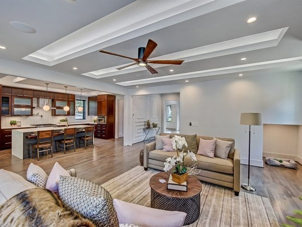 Modern home with living room, accent lighting, recessed lighting, light hardwood floor, sofa, and console tables. Living room has dog nook under the stairs Photo 10 of Contemporary Craftsman Home