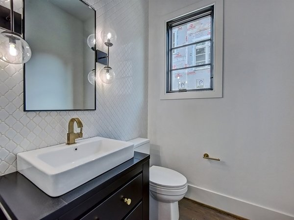 Modern home with bath room, light hardwood floor, one piece toilet, ceramic tile wall, and vessel sink. Powder room with accent wall Photo 12 of Contemporary Craftsman Home
