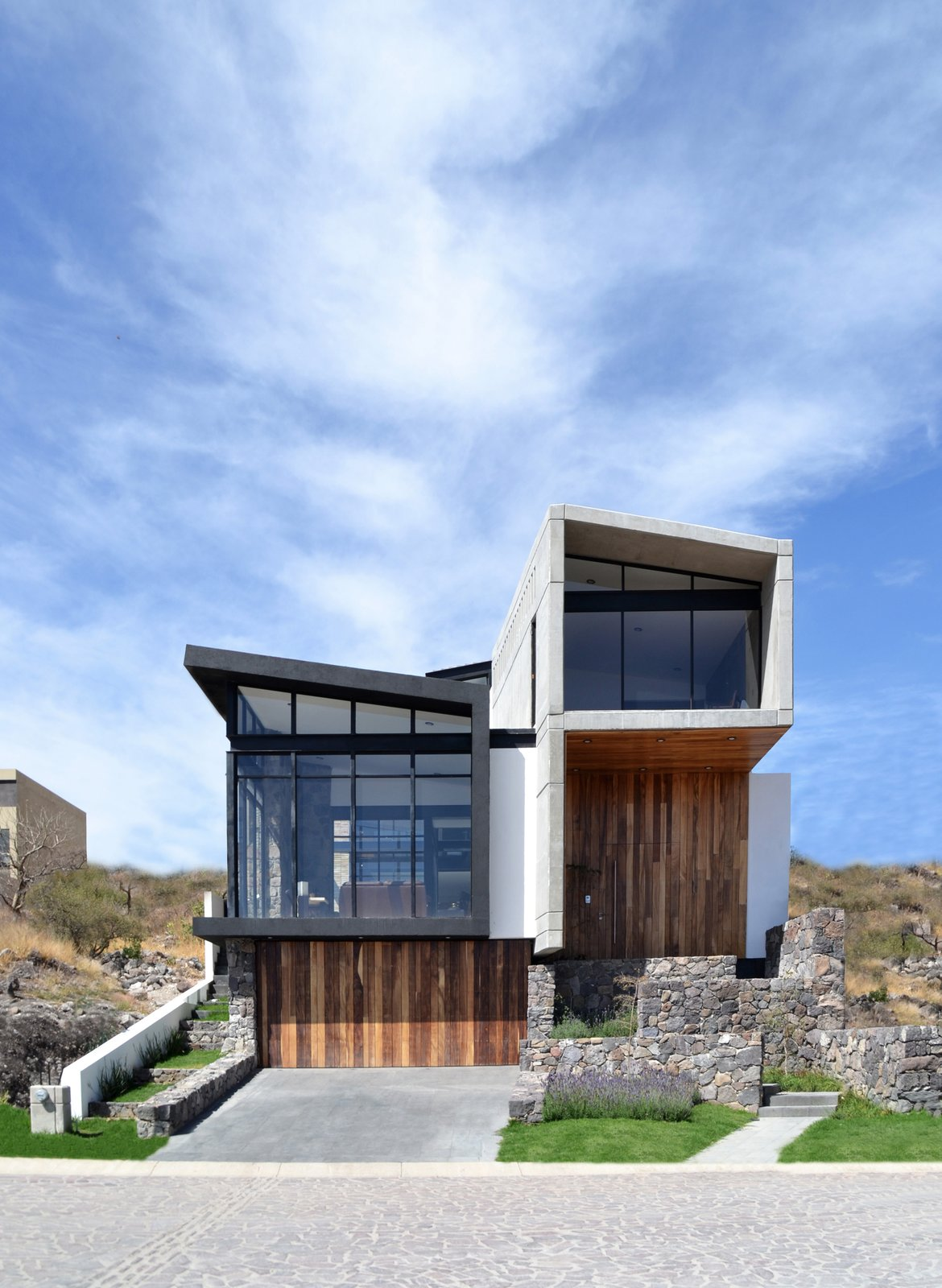 East Facade Tagged: Outdoor, Front Yard, Horizontal Fences, Wall, Slope, Grass, and Landscape Lighting.  Casa AB by e|arquitectos