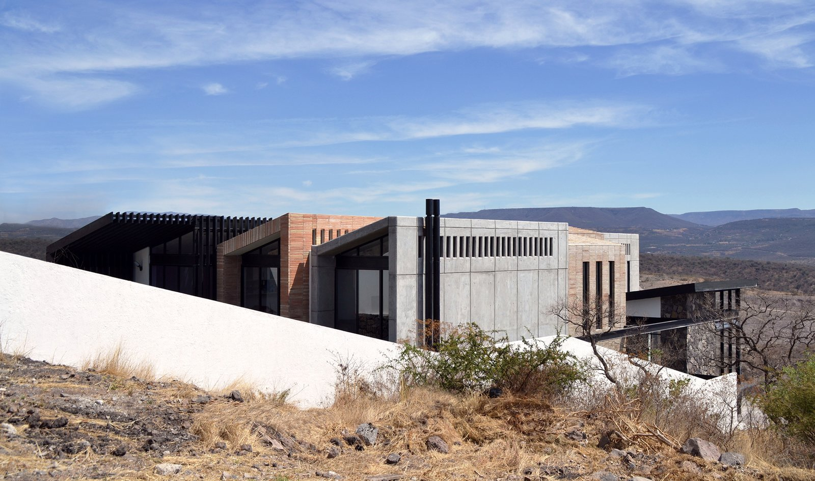 Southwest Facade Tagged: Outdoor, Grass, Hardscapes, and Slope.  Casa AB by e|arquitectos