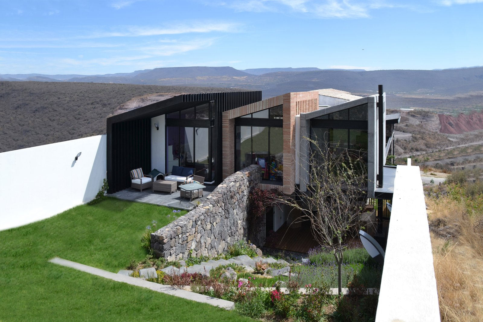 West Facade Tagged: Outdoor, Field, Garden, Back Yard, Slope, Grass, Gardens, Flowers, Stone Patio, Porch, Deck, Walkways, Decking Patio, Porch, Deck, and Wood Patio, Porch, Deck.  Casa AB by e|arquitectos