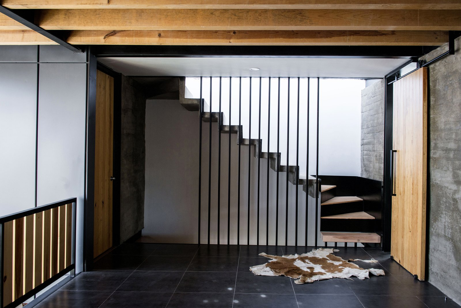 TV Room and Stairs Tagged: Staircase, Concrete Tread, Metal Tread, Metal Railing, and Wood Tread.  Casa MA by e|arquitectos