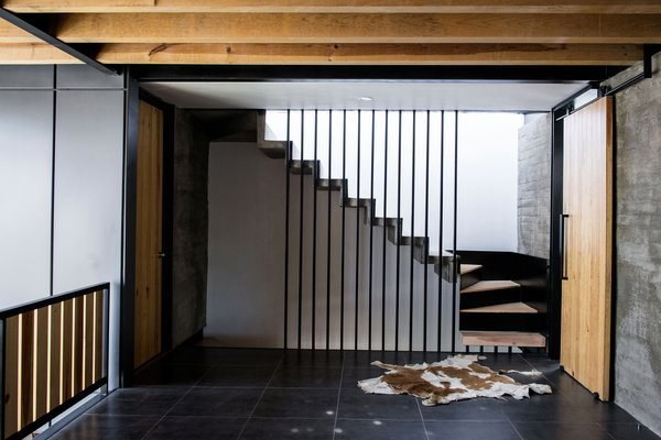 Modern home with staircase, concrete tread, metal tread, metal railing, and wood tread. TV Room and Stairs Photo 17 of Casa MA