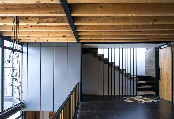 Modern home with staircase, wood tread, concrete tread, metal tread, and metal railing. Double Height - TV Room - Stairs Photo 16 of Casa MA
