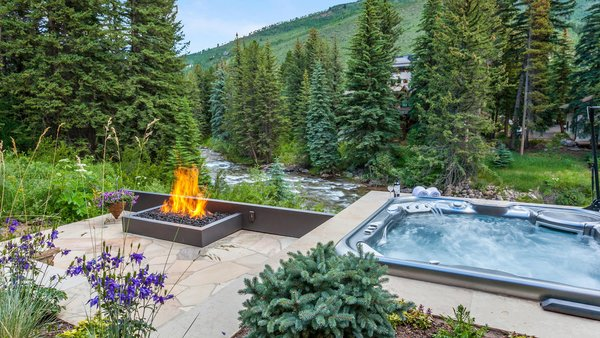 Modern home with outdoor, trees, boulders, shrubs, flowers, walkways, landscape lighting, large patio, porch, deck, stone patio, porch, deck, and post lighting. Vail, Colorado on Gore Creek Photo 19 of Beaver Dam Luxury