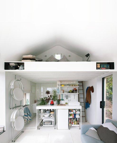Modern home with kitchen, tile counter, white cabinet, ceramic tile backsplashe, refrigerator, ceiling lighting, and vessel sink. @aubry.guillaume Photo  of Viking Seaside Summer Cabin