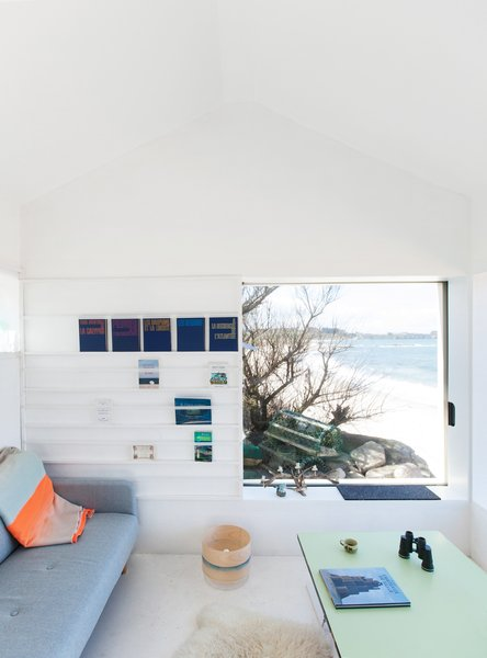Modern home with living room, sofa, bookcase, and concrete floor. @aubry.guillaume Photo 5 of Viking Seaside Summer Cabin