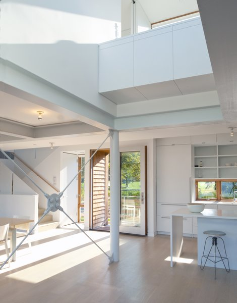 Modern home with kitchen, engineered quartz counter, white cabinet, light hardwood floor, ceiling lighting, and refrigerator. A view back to the front door and kitchen.  The desk is above in the double height space. Photo 3 of Chesapeake Bay House