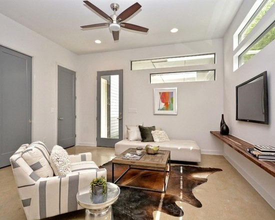 Modern home with living room, bench, ottomans, chair, sofa, coffee tables, end tables, console tables, ceiling lighting, sectional, recliner, bookcase, recessed lighting, and concrete floor. Photo 8 of 809 W. Live Oak