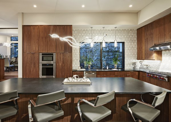Modern home with granite counter, wood cabinet, light hardwood floor, marble backsplashe, pendant lighting, wall oven, range hood, recessed lighting, dishwasher, microwave, cooktops, undermount sink, accent lighting, dining room, stools, bar, and storage. kitchen Photo 7 of Westlake4