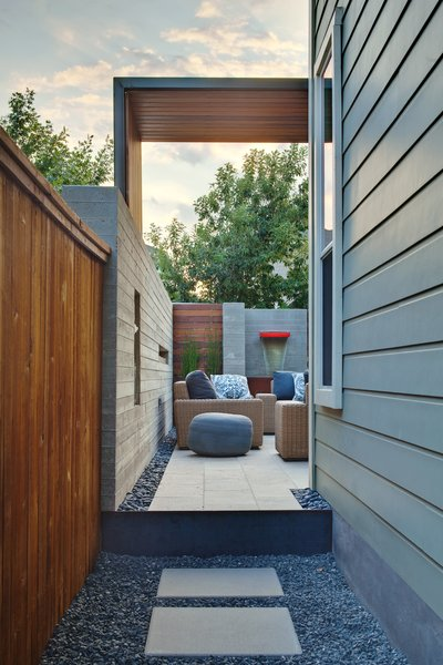 Modern home with chair, ottomans, sofa, floor lighting, outdoor, travertine floor, back yard, shrubs, gardens, walkways, raised planters, hardscapes, large patio, porch, deck, stone patio, porch, deck, horizontal fence, small pool, concrete pool, landscape lighting, vertical fence, and wood fence. side yard entry Photo  of Mueller 1