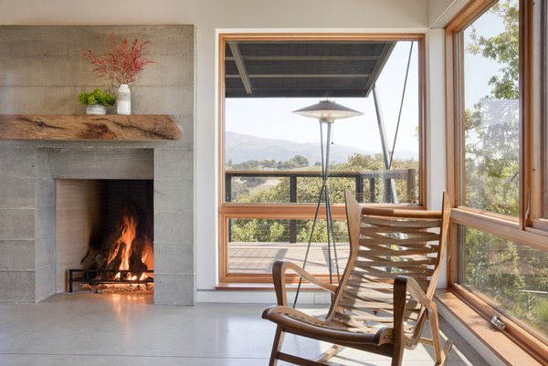 Modern home with living room, chair, concrete floor, standard layout fireplace, floor lighting, and wood burning fireplace. Photo 4 of Santa Ynez House