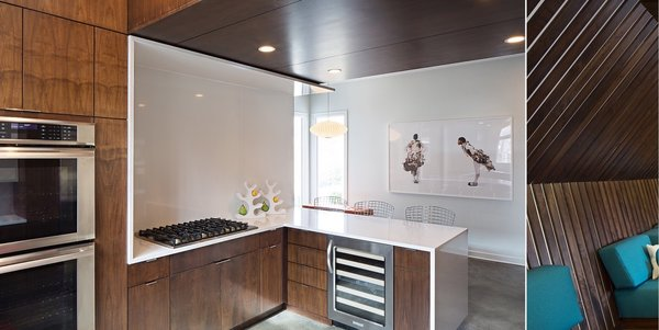 Modern home with kitchen, stone counter, wood cabinet, white cabinet, laminate cabinet, concrete floor, refrigerator, recessed lighting, wine cooler, microwave, pendant lighting, wall oven, dishwasher, cooktops, range, beverage center, and undermount sink. Photo 3 of MEK RESIDENCE