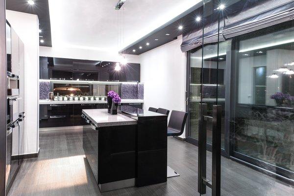 Modern home with kitchen, track lighting, white cabinet, granite counter, wall oven, and medium hardwood floor. Photo 9 of Voluntari Residence