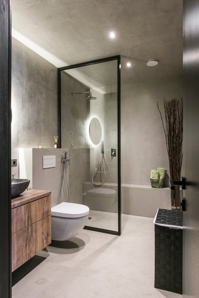 Modern home with bath room, concrete floor, vessel sink, laminate counter, open shower, accent lighting, ceiling lighting, concrete wall, and one piece toilet. Photo  of Drills&Hollywood