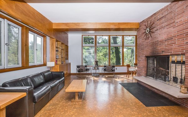 Modern home with living room, bench, bookcase, sofa, ceiling lighting, track lighting, accent lighting, wood burning fireplace, and cork floor. Living Room Photo 5 of Classic Mid Century Modern home for sale