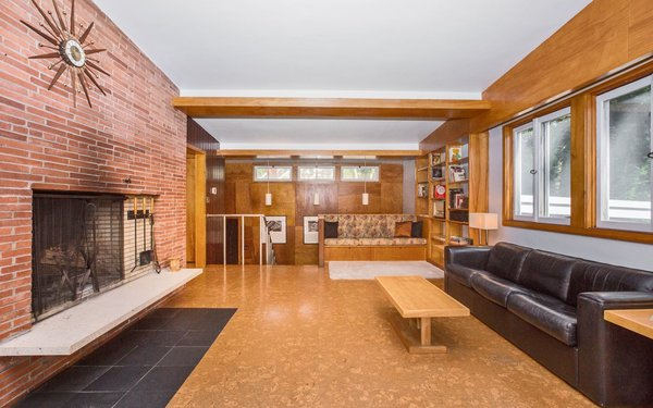 Modern home with living room, bookcase, ceiling lighting, track lighting, accent lighting, bench, cork floor, and wood burning fireplace. Living Room Photo 6 of Classic Mid Century Modern home for sale