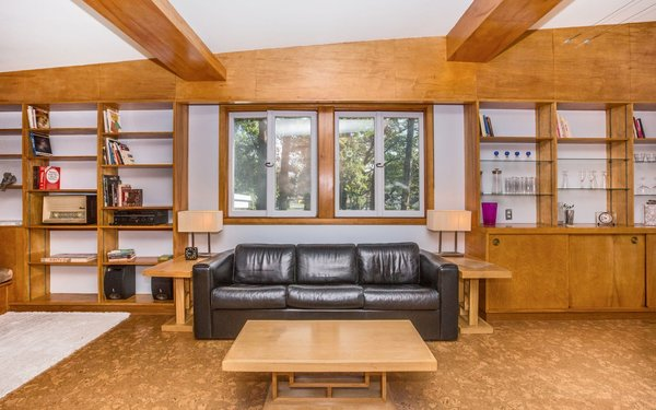 Modern home with living room, bookcase, sofa, end tables, coffee tables, bench, track lighting, table lighting, wood burning fireplace, accent lighting, and cork floor. Living Room Photo 7 of Classic Mid Century Modern home for sale
