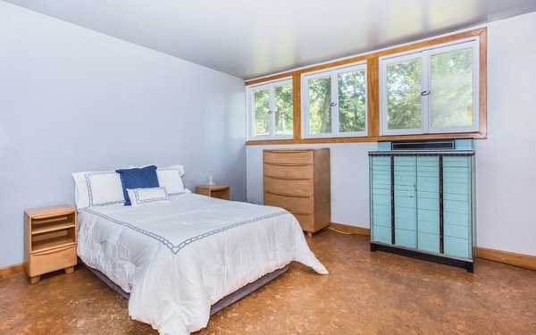 Modern home with bedroom, bed, dresser, shelves, night stands, accent lighting, storage, ceiling lighting, and cork floor. Bedroom 1 Photo 16 of Classic Mid Century Modern home for sale