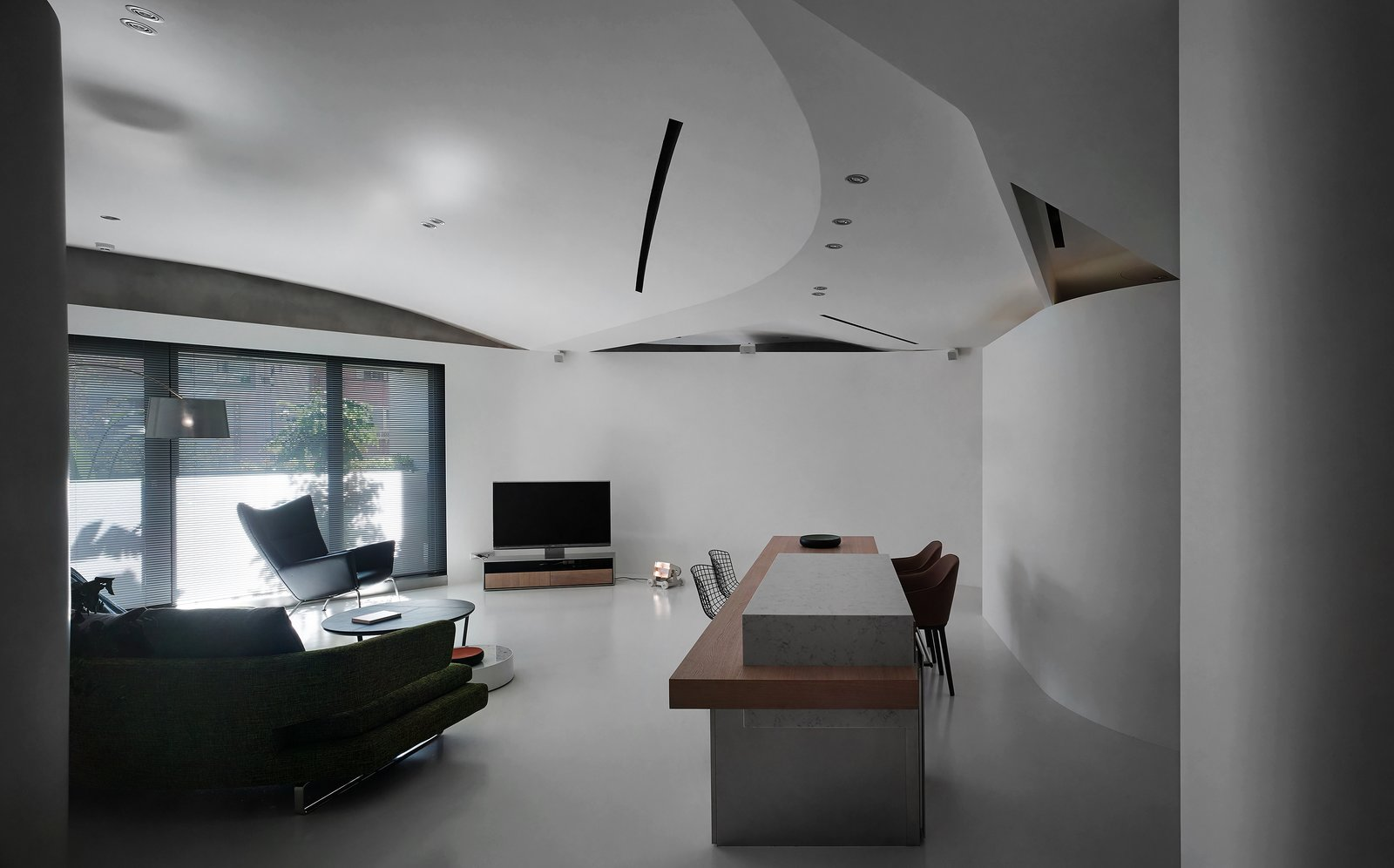 The ceiling is a composite of several curved surfaces, the seams of which implicitly implying the activities underneath.  Tagged: Living Room, Chair, Sofa, Bar, Table, Lamps, Ceiling Lighting, Wall Lighting, and Concrete Floor.  Fluid House by shi-chieh lu