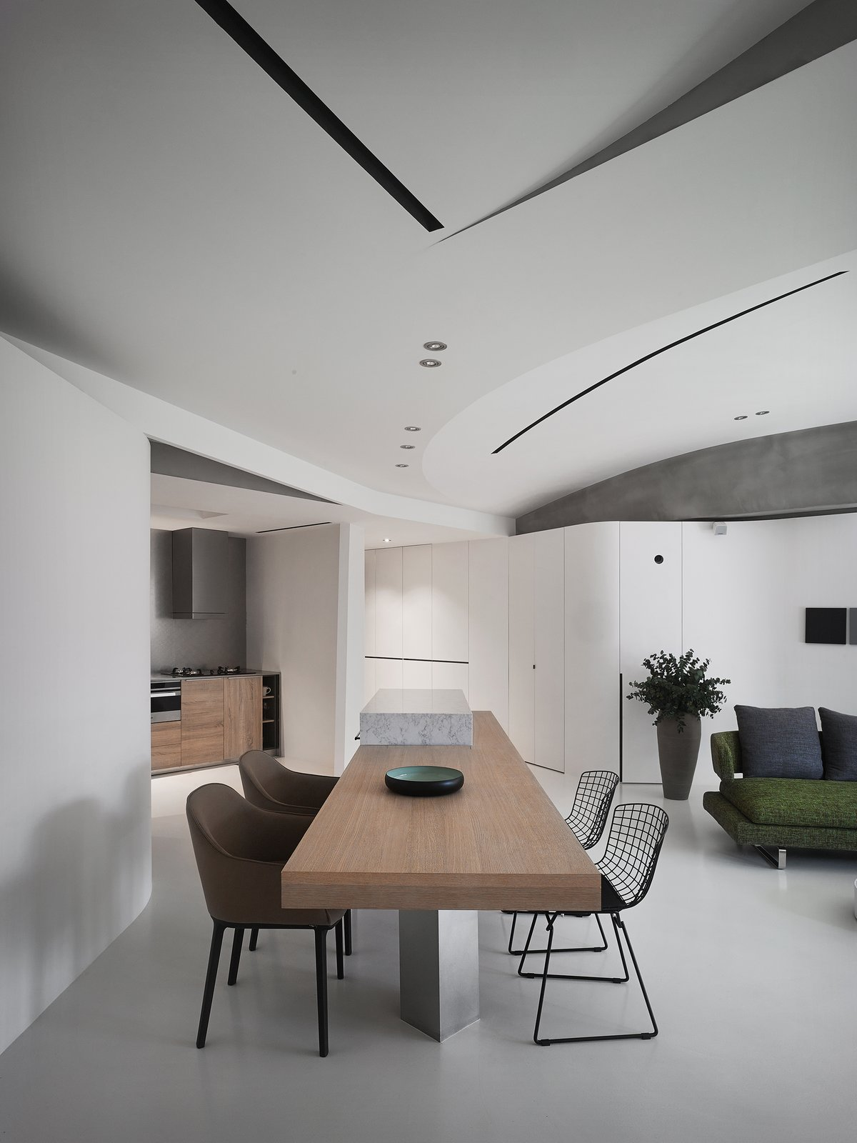 The living space is equipped with a home cinema and a mini bar to enhance the entertainment facilities for social activities.  Tagged: Dining Room, Chair, Ceiling Lighting, Table, Bar, and Concrete Floor.  Fluid House by shi-chieh lu