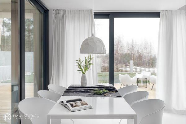 Modern home with dining room, chair, table, pendant lighting, and lamps. Photo 6 of Minimal Seaside Villa