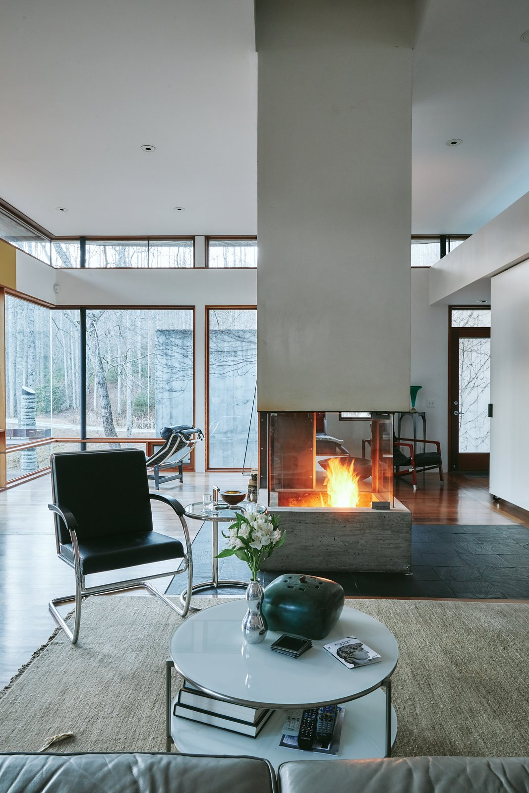 'Mountain House' - Winter Living Tagged: Living Room, Medium Hardwood Floor, Two-Sided Fireplace, and Wood Burning Fireplace.  Mountain House Modern