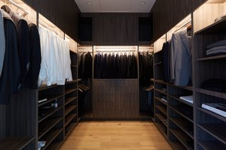 10 Modern Walk-In Closets - Photo 8 of 10 - The dramatic design of this master walk-in closet is created with dark wood and warm lighting.