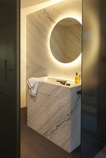 8 Spa-Like Bathrooms Designed to Instantly Soothe - Photo 1 of 8 - A glowing mirror, wall-to-wall marble, and a hefty-yet-delicate sink in this bathroom by interior design firm Roomdresser oozes a mixture of clean lines and carefully lit surfaces for a relaxing, calming experience.
