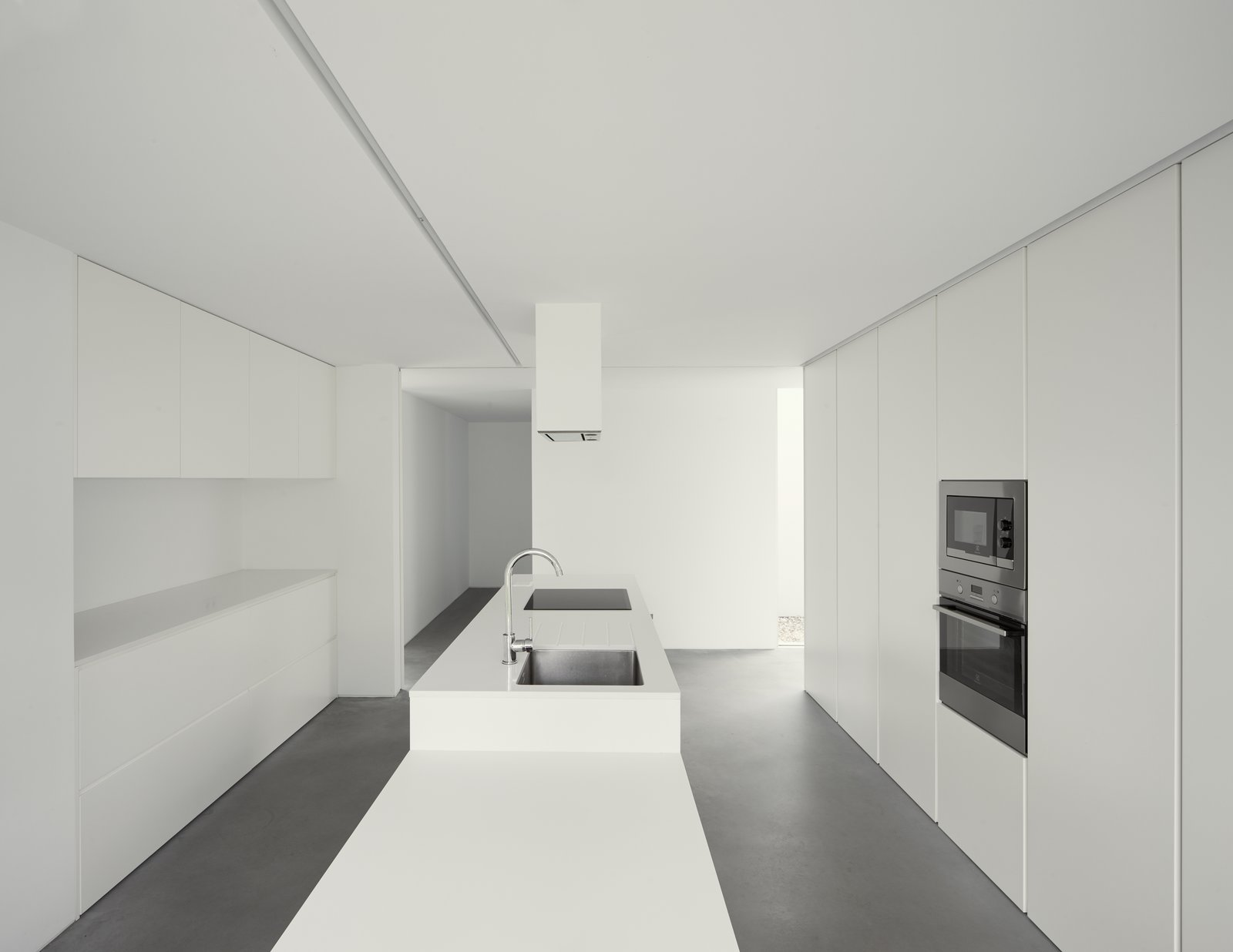 Tagged: Kitchen, Engineered Quartz Counter, White Cabinet, Concrete Floor, Cooktops, Undermount Sink, and Wall Oven. Fanu House by Bruno Lucas