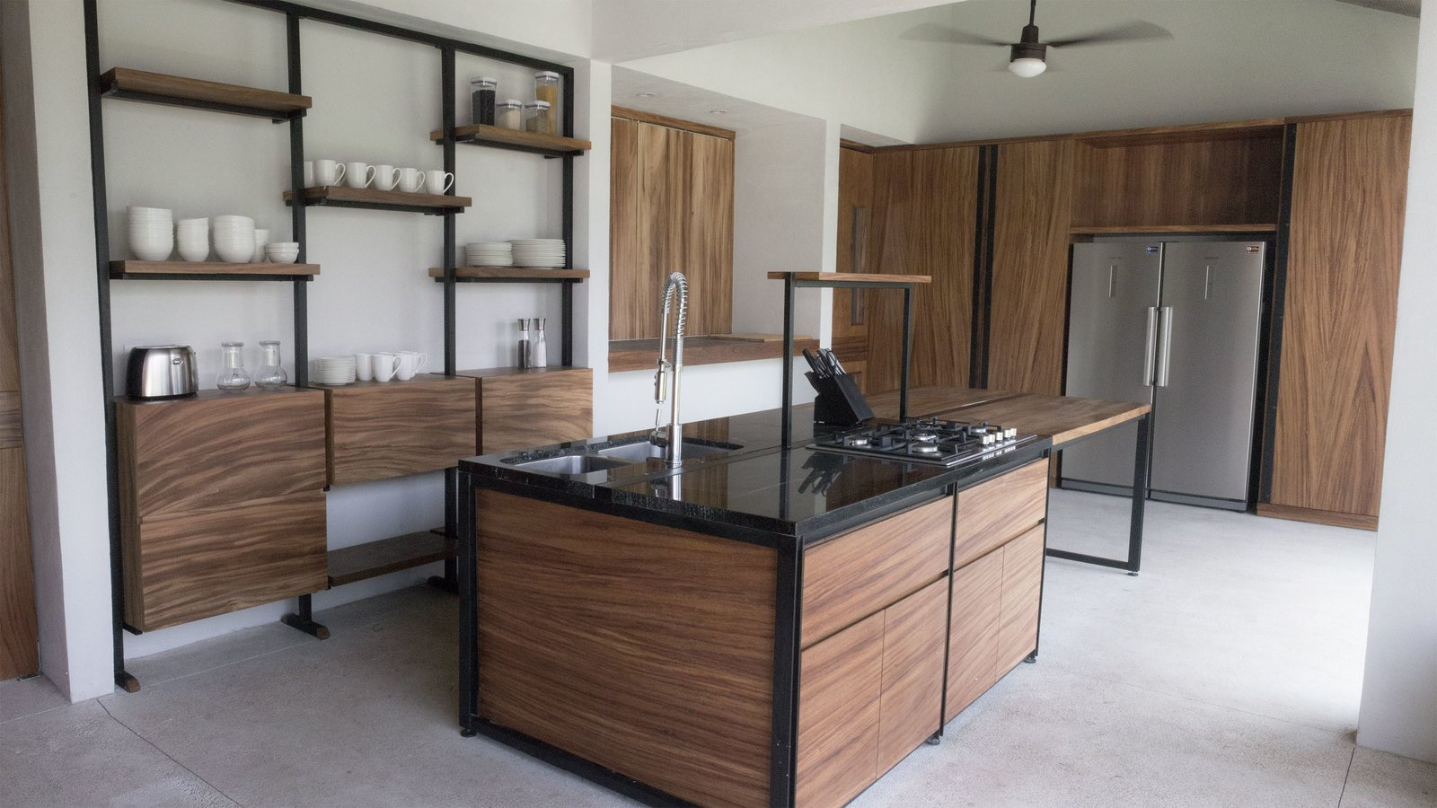 Tagged: Kitchen, Granite Counter, Wood Counter, Metal Counter, Metal Cabinet, Refrigerator, Wood Cabinet, Concrete Floor, Microwave, Dishwasher, and Wall Oven.  Casa Paraíso by DCPP by LCMX