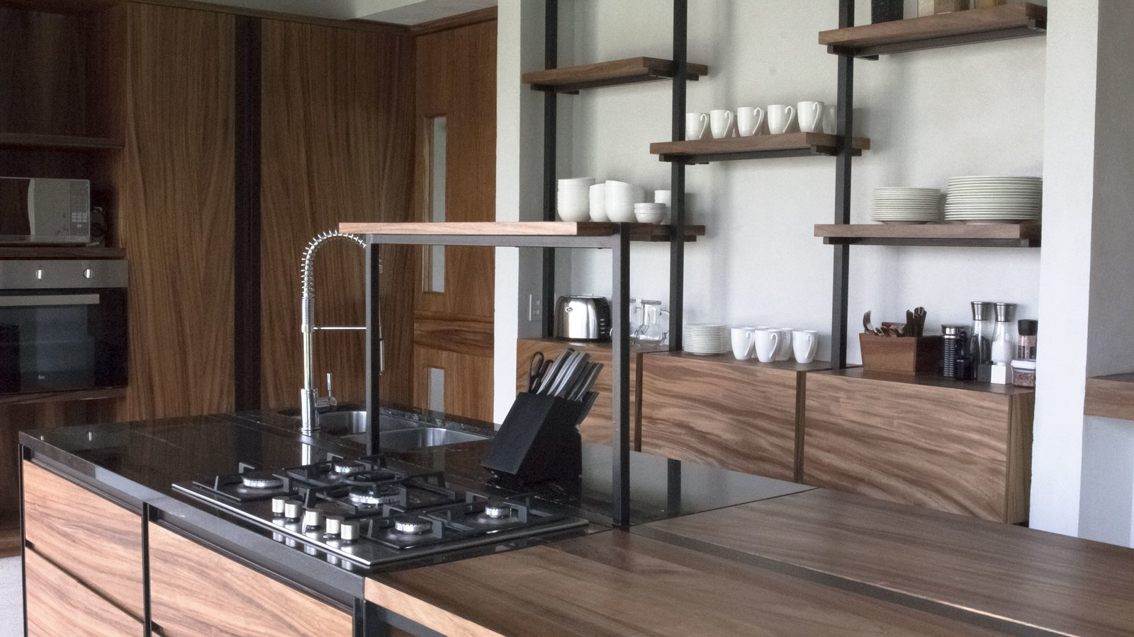 Tagged: Kitchen, Granite Counter, Wood Counter, Metal Counter, Concrete Floor, Wood Cabinet, Refrigerator, Microwave, Wall Oven, and Dishwasher.  Casa Paraíso by DCPP by LCMX