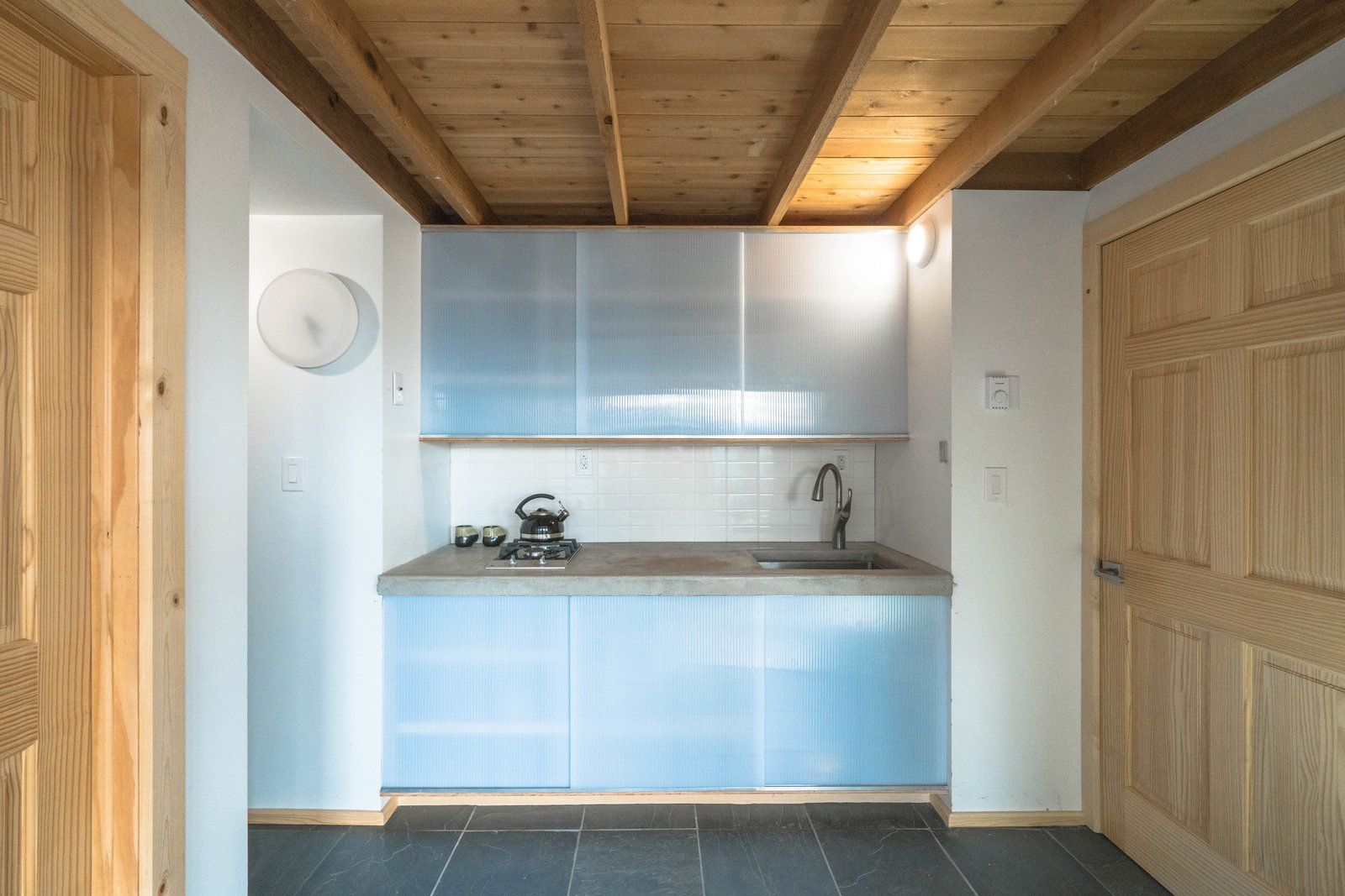 Tagged: Kitchen, Concrete Counter, Wood Cabinet, Slate Floor, Ceramic Tile Backsplashe, Wall Lighting, Cooktops, and Undermount Sink.  MARTaK Passive House by Baosol Design