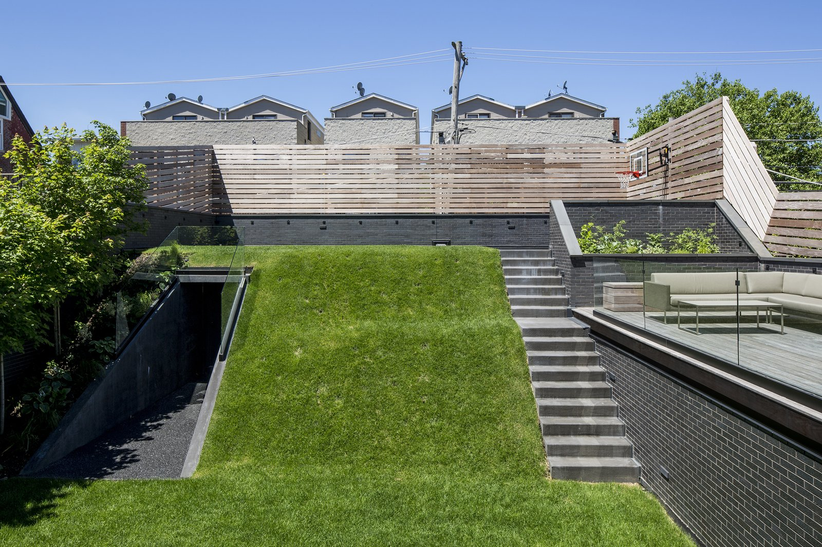 """Play surface and """"hill"""" covers garage Tagged: Outdoor, Grass, Trees, Back Yard, Horizontal Fences, Wall, Wood Patio, Porch, Deck, Wood Fences, Wall, and Slope.  Mohawk House by UrbanLab"""