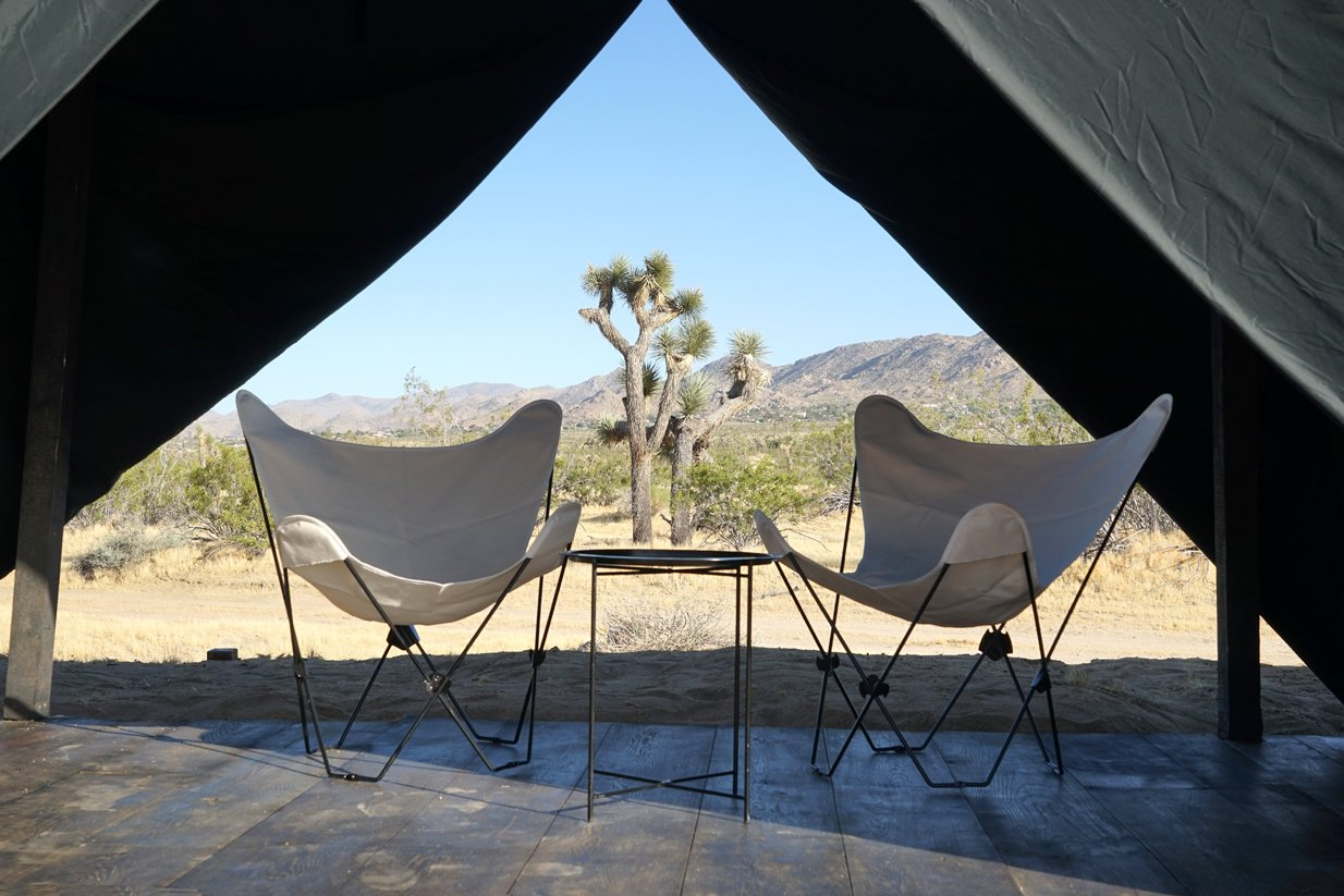 Folding canvas butterfly chairs and table Tagged: Living Room, Chair, Coffee Tables, and Dark Hardwood Floor. Joshua Tree Case Study Cabin by Mike Vensel