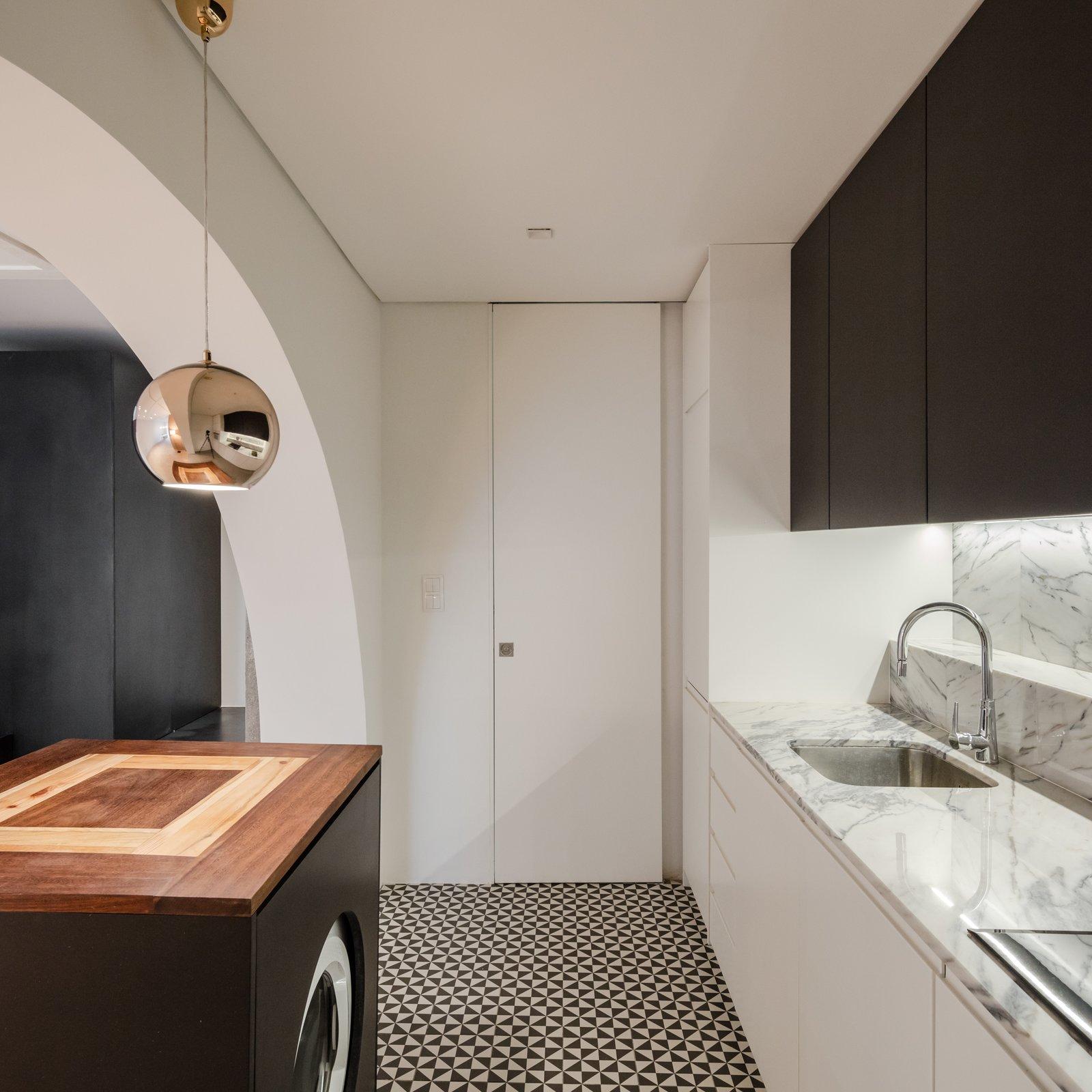 Tagged: Kitchen, Marble Counter, Wood Cabinet, White Cabinet, Ceramic Tile Floor, Stone Slab Backsplashe, Undermount Sink, and Pendant Lighting.  Rua Maria Loft by KEMA studio