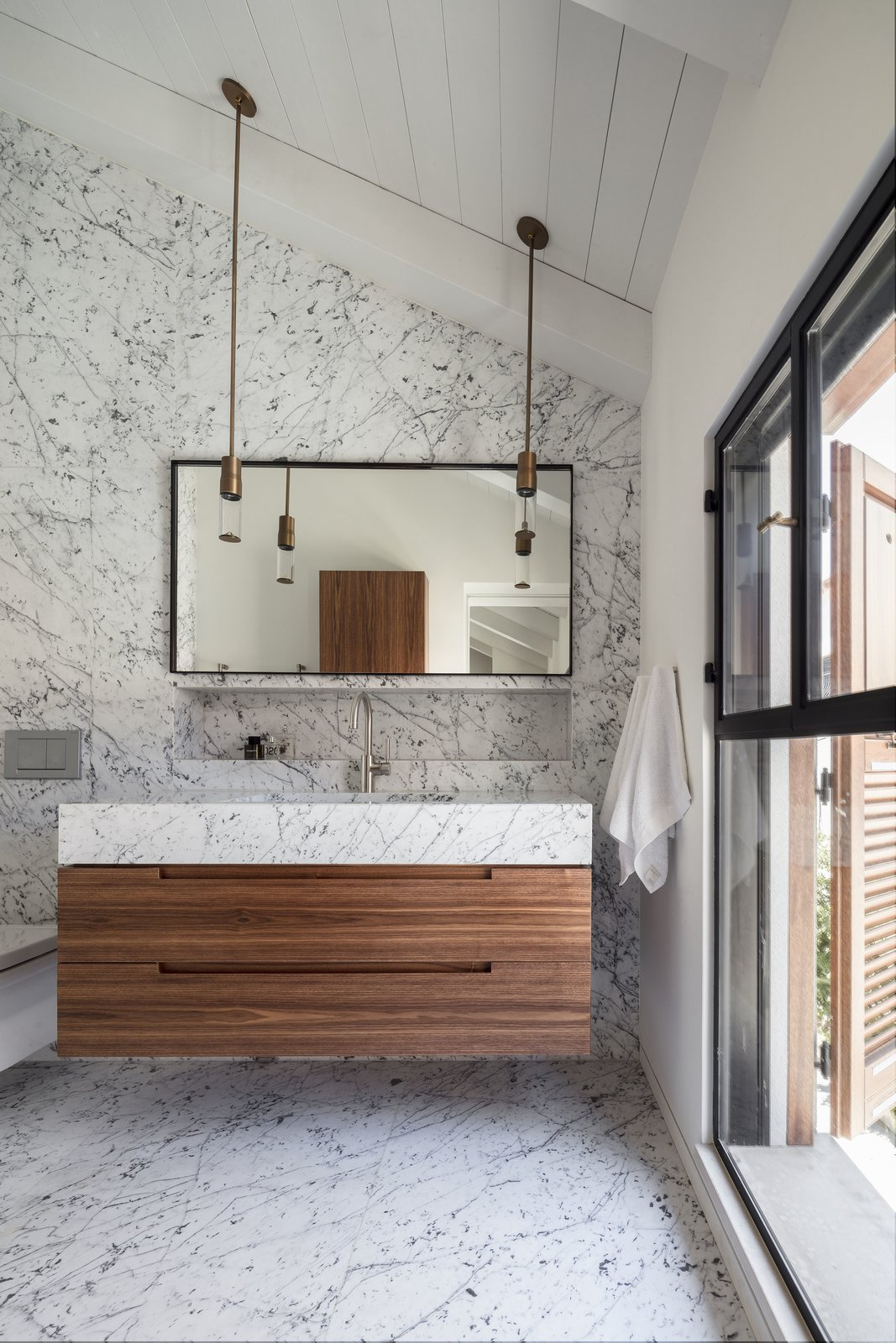 The Charm Townhouse - Master bathroom - cut to size 'Carrara Bianco' tiles intensifying the high ceiling Tagged: Marble, Undermount, Marble, Full, Pendant, Marble, One Piece, Storage, and Cabinet.  Best Storage Pendant Marble Photos from The Charm Townhouse