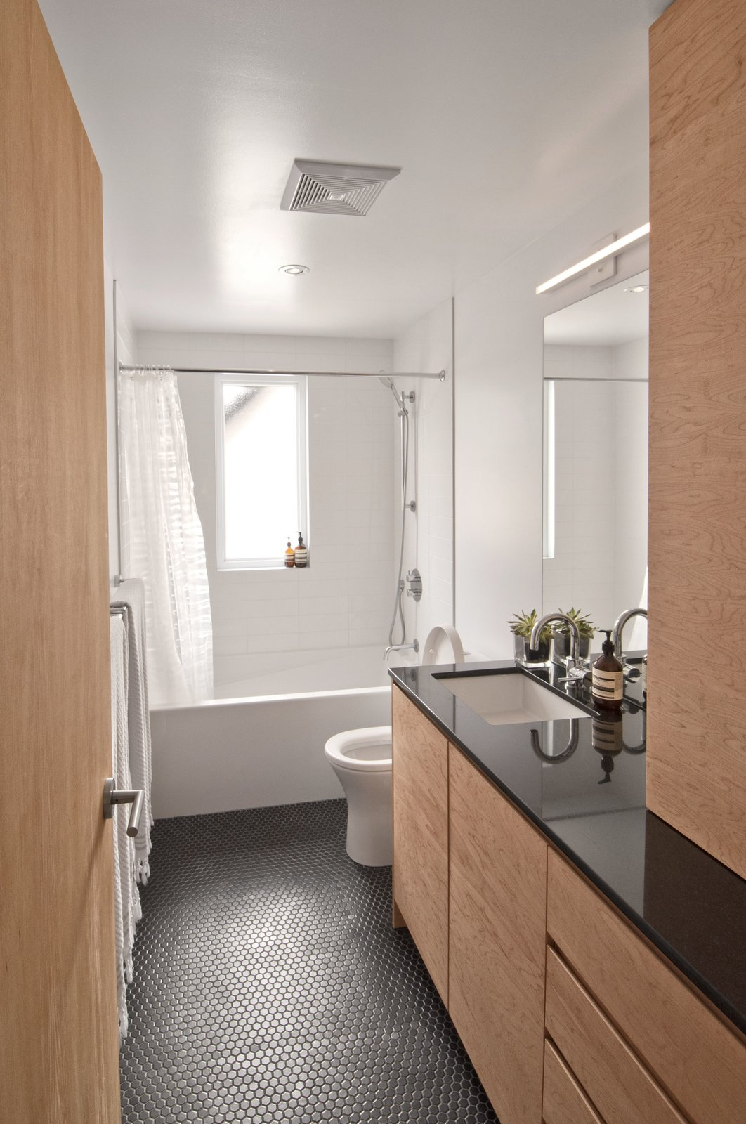 Tagged: Bath Room, Undermount Sink, Porcelain Tile Floor, Granite Counter, Alcove Tub, Open Shower, Recessed Lighting, Ceramic Tile Wall, and Two Piece Toilet.  Fabre Residence by Jonathan Dorthe