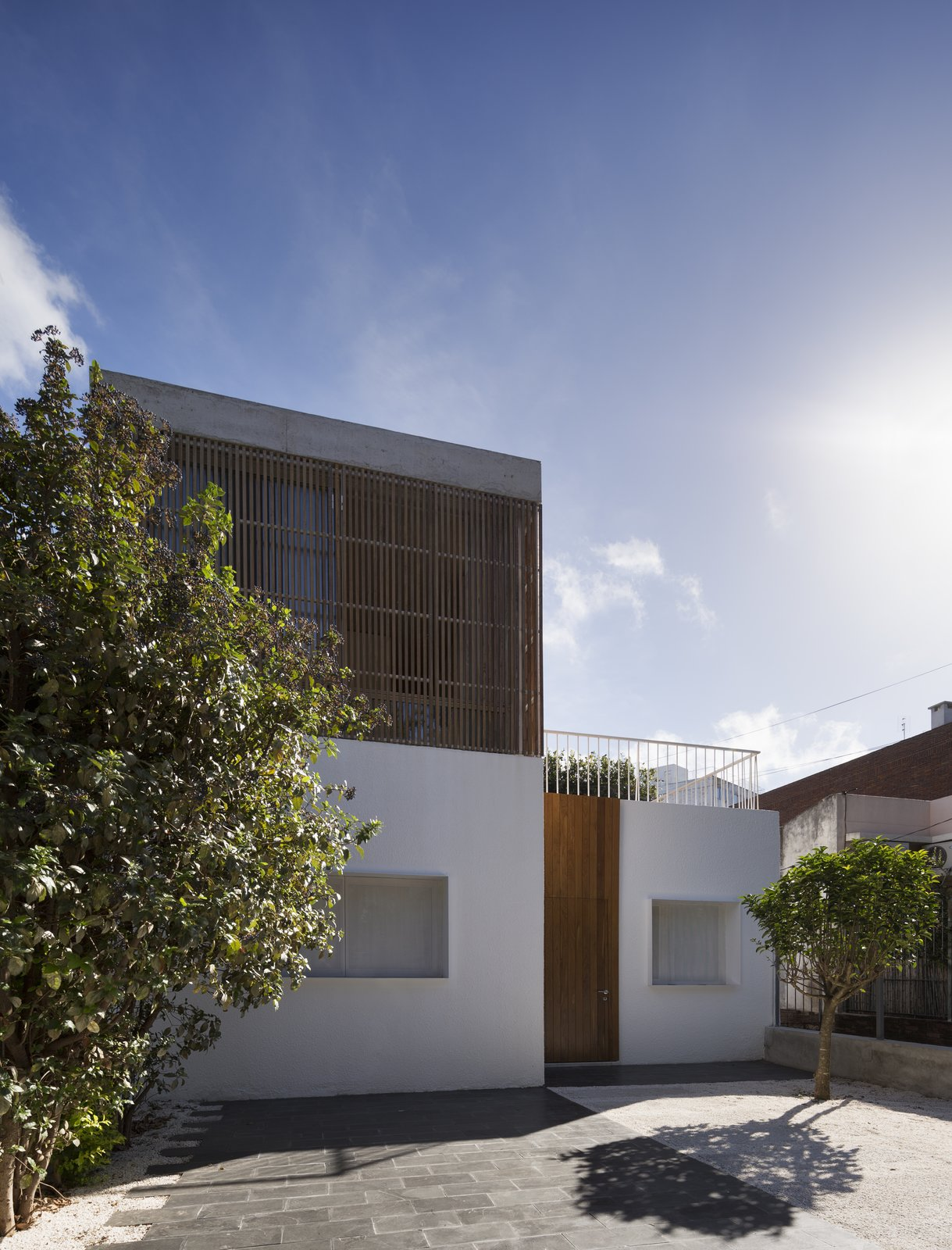 Facade Tagged: Outdoor, Front Yard, Trees, Walkways, Small Patio, Porch, Deck, Vegetables, Flowers, Gardens, Wood Patio, Porch, Deck, Concrete Patio, Porch, Deck, Wood Fences, Wall, and Tile Patio, Porch, Deck.  Casa Plaza by mass arquitectos