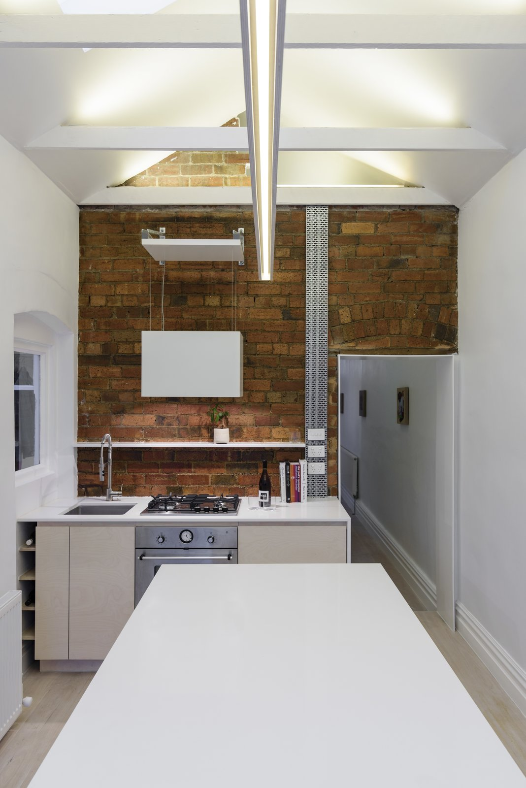 Kitchen (Night) Tagged: Kitchen, Engineered Quartz Counter, Wood Cabinet, Light Hardwood Floor, Ceiling Lighting, Pendant Lighting, Brick Backsplashe, Recessed Lighting, Accent Lighting, Wall Oven, Cooktops, Range, Range Hood, and Undermount Sink. Curtain Cottage by Otto Henkell