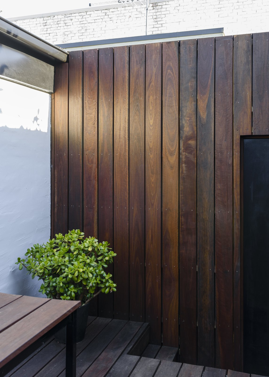 Courtyard wall detail Tagged: Outdoor, Back Yard, Shrubs, Small Patio, Porch, Deck, Hardscapes, Gardens, Decking Patio, Porch, Deck, Planters Patio, Porch, Deck, Wood Fences, Wall, and Wood Patio, Porch, Deck.  Curtain Cottage by Otto Henkell