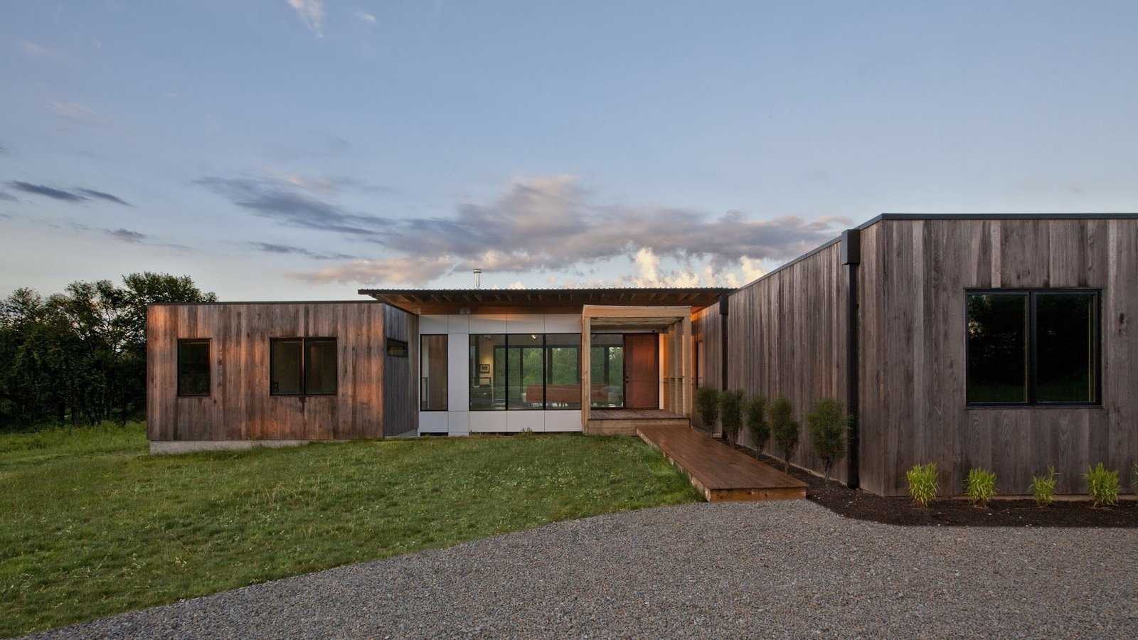 Sunrise at Copperwood. The exterior is comprised of thermally treated Ash and white, cement panels.  Tagged: Outdoor, Grass, Field, Shrubs, Front Yard, Hardscapes, Trees, Decking Patio, Porch, Deck, and Large Patio, Porch, Deck.  Copperwood by Kevin Swan
