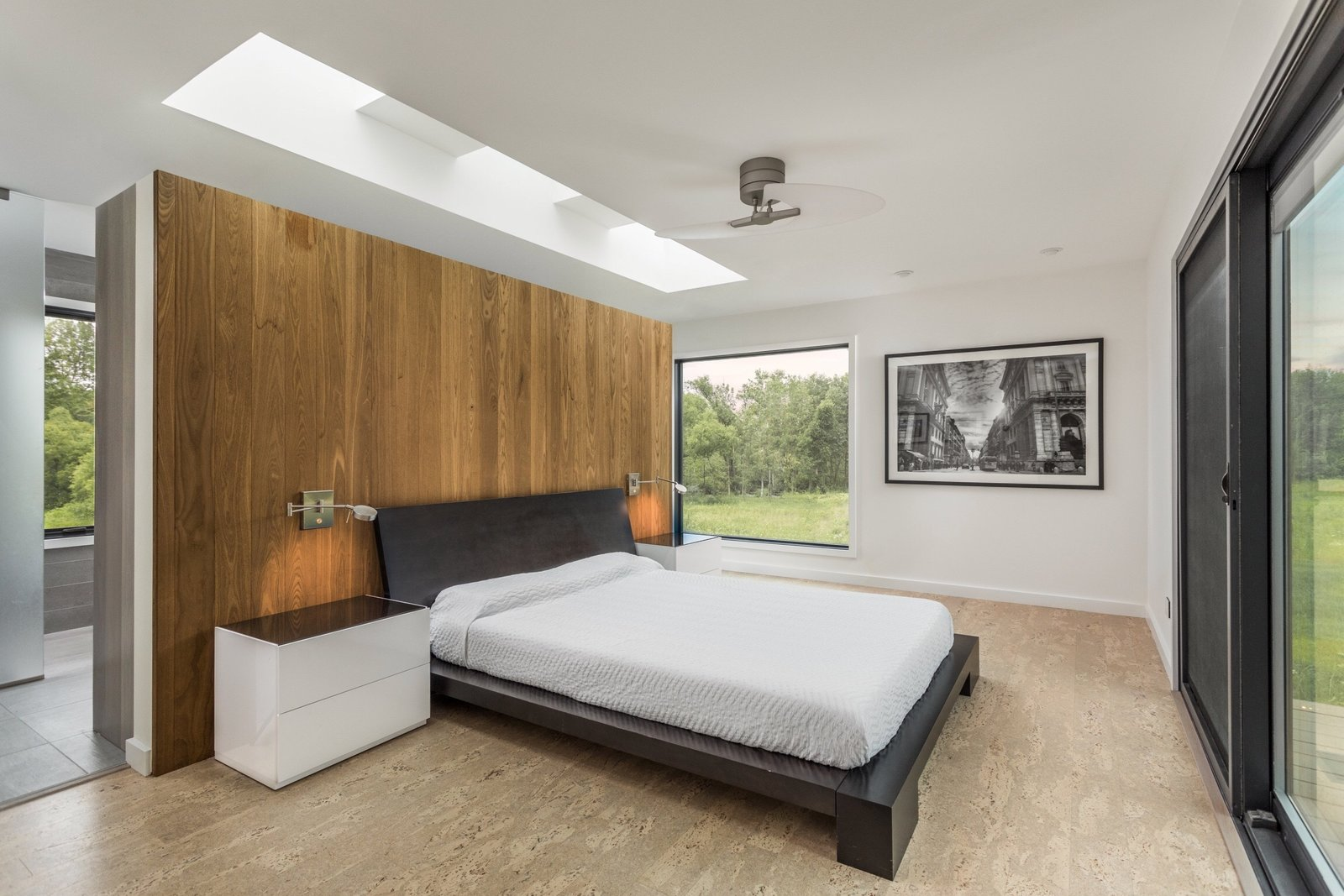 The bedroom features a floating wall, with beautiful views on three sides.  Tagged: Bedroom, Bed, Night Stands, Ceiling Lighting, Recessed Lighting, Cork Floor, and Cement Tile Floor.  Copperwood by Kevin Swan