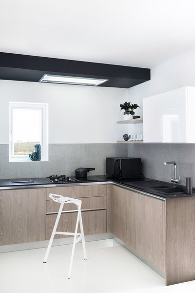 The narrow kitchen highlights a ceiling concealed hood from Falmec, overlooking a black granite countertop with the domino mix of barbecue + gas + induction hobs from Siemens, sitting atop handle less grey wood cabinets. On the open shelves, the cups are characterized by Japanese brush strokes and Finnish form, designed by Norm Architects for Menu. The vase by Agnes Fries for Normann Copenhagen features contrasting brush strokes in black over a clean white form, and adorns the top shelf along with beautiful black lilies to go with. Among other details are the grey Birillo dispenser from Alessi for soap, the Tumbler Clock by Menu as the kitchen timer, and adding to the green is the Cacti from Hay Design overlooking the small window.
