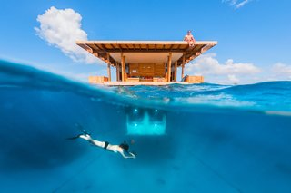 "A New Book For Those Who Dream of Living in a Floating Home - Photo 11 of 11 - Off the coast of Tanzania in the Indian Ocean, Manta Resort's ""Underwater Room"" is a three-level suite surrounded by a coral reef. Below water, guests can watch marine life—while on the rooftop deck, they can soak up the sun."