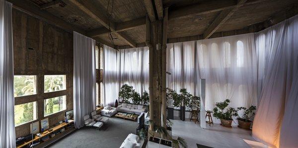 The voluminous living room has plenty of windows, letting in an abundance of natural light.